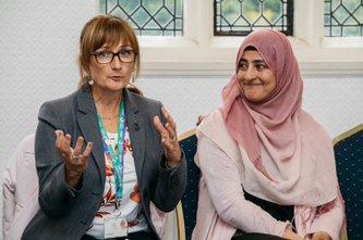 Two women speaking during community meeting