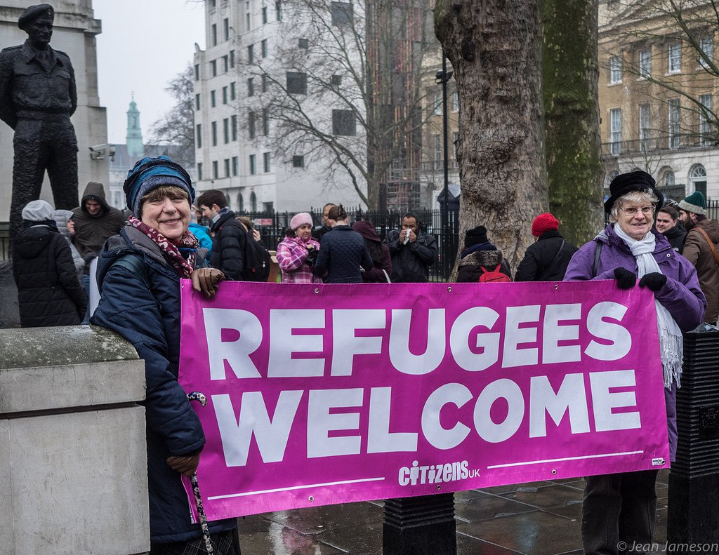 Women holding banner at Refugees Welcome public action