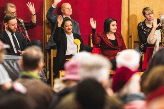 Group at public meeting raising hands
