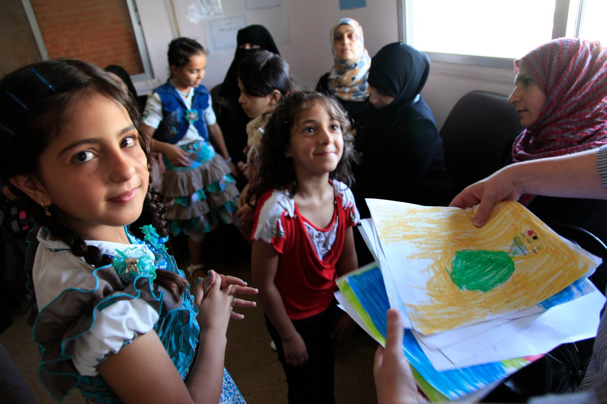 Young refugee children smiling and handing in drawings
