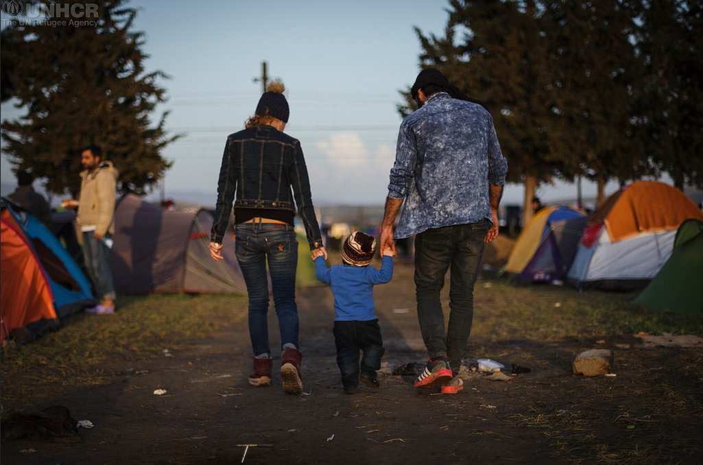 Refugee family holding hands at camp site
